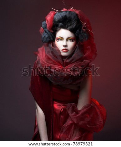Young woman with creative visage in red dress and  shawl. - stock photo