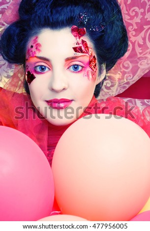 Young woman with creative visage posing with balloons
