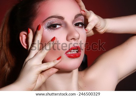 Young woman with creative visage. Red fon. Fashion