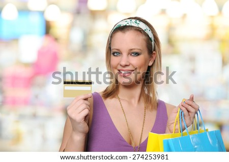 Young woman with credit card and bags shopping inside a mall - stock photo