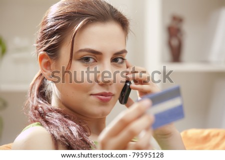 young woman with credit card and mobile phone - stock photo