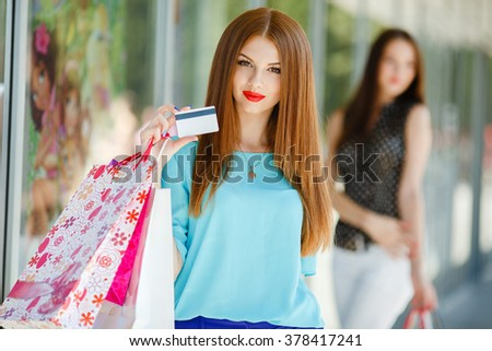 Young woman with credit card and shopping bags. Portrait of a young woman holding shopping bags and a credit card. Young woman with shopping bag and card in store - stock photo