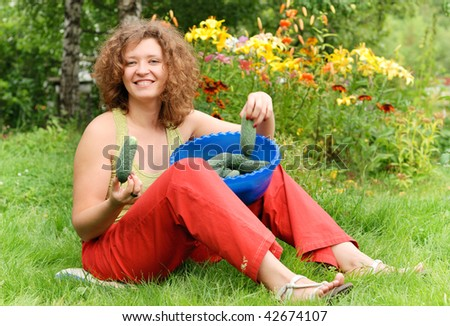 Young woman with crop of cucumbers in garden - stock photo