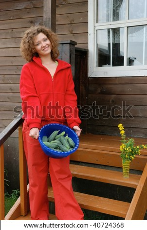 Young woman with crop of cucumbers near house - stock photo