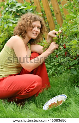 Young woman with crop of red currant in garden - stock photo