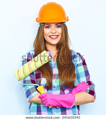 Young woman with crossed arms holding painting roller, standing against white background wall. Studio portrait of smiling woman. - stock photo