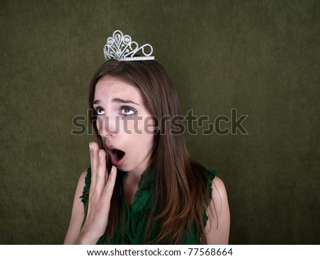 Young woman with crown on green background yawns - stock photo