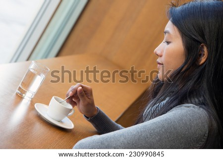 Young woman with cup in a restaurant - stock photo