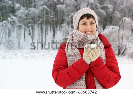 Young woman with cup in winter park - stock photo