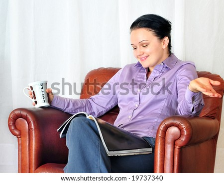 young woman with cup of coffee looking very surprised - stock photo