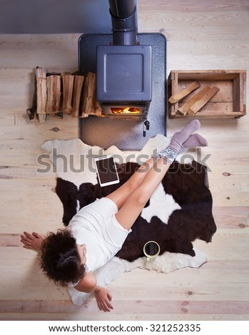 Young woman with cup of coffee sitting home on a cow rug by the fireplace. Fall winter relaxing and leisure concept. - stock photo