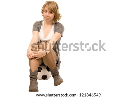 Young woman with curly blonde hair wearing shorts sitting on a football with her hands clasped over her knees looking at the camera, studio portrait on white - stock photo