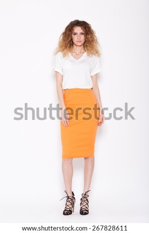 young woman with curly hair posing in an orange skirt and white tshirt on white background - stock photo