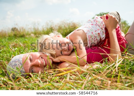 Young woman with cute little girl enjoying a summer day outdoors - stock photo