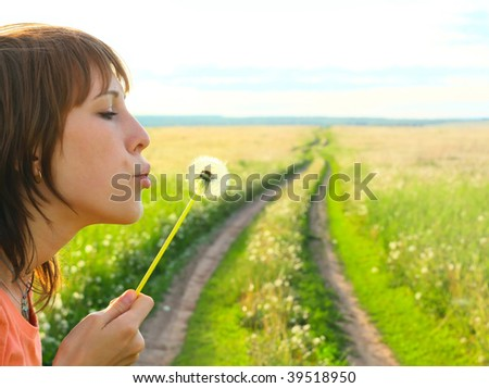 Young woman with dandelion