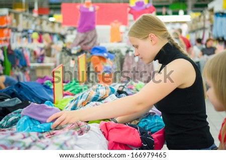 Young woman with daughter select skirts and clothes in supermarket - stock photo