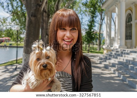 Young woman with decorative dog on hands looking very happy and exited, copy space - stock photo