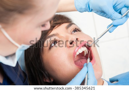 Young woman with dentist in a dental clinic doing orthodontic exam to prevent caries - stock photo