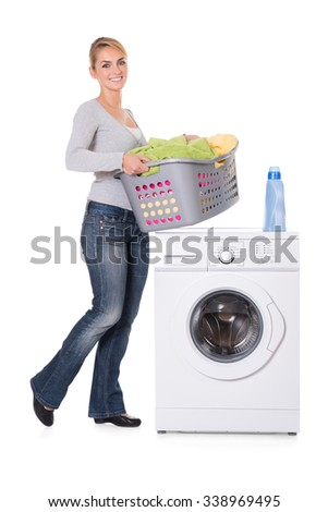 Young woman with detergent and laundry standing by washing machine over white background - stock photo