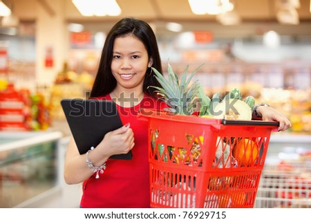 Young woman with digital tablet holding fruit basket in shopping centre and looking at camera - stock photo