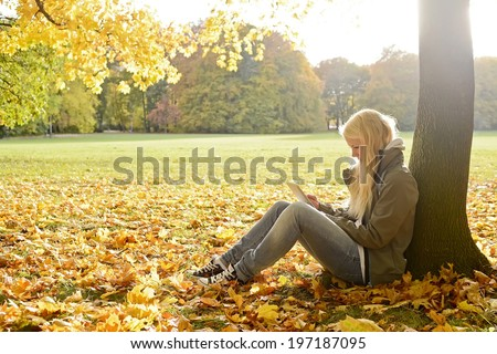 young woman with digital tablet in autumn park - stock photo
