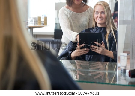 Young woman with digital tablet showing hairstyle to hair dresser - stock photo