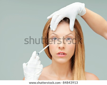 young woman with doctor hands injecting - stock photo