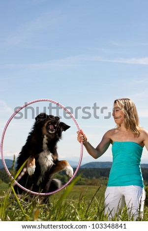Young woman with dog and tires on a lawn. In the background mountains - stock photo