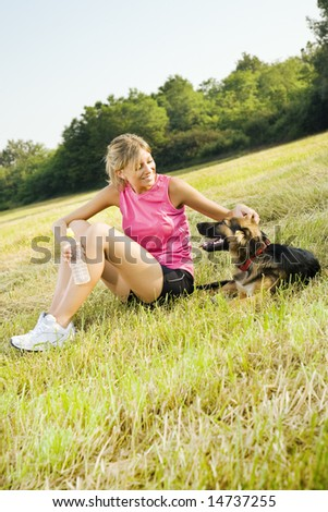 Young woman with dog relaxing in park - stock photo