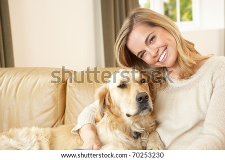 Young woman with dog sitting on sofa - stock photo