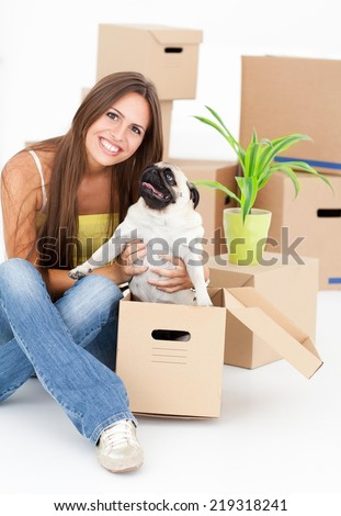 Young woman with dog surrounded by boxes moving into her new home. - stock photo