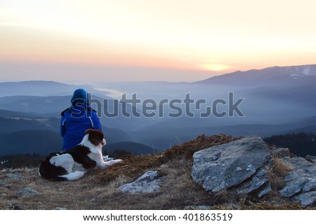 Young woman with dog watching sunrise high in the mountain - stock photo