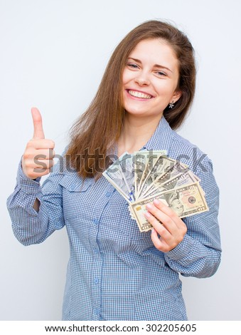Young woman with dollars gesturing thumbs up - stock photo