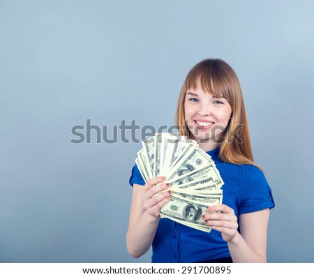 Young woman with dollars in her hands. Happy young woman hold money one hundred dollar bills in hand on the blue wall background. Portrait of a happy woman with a fan of american dollar currency notes - stock photo