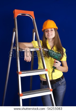 young woman with drill near on scaling-ladder over blue
