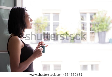 Young woman with drink standing at an open window. Woman drinking a beverage from a mug at the window. A woman with beverage in cup looks out the window at the street. Morning coffee in Paris.