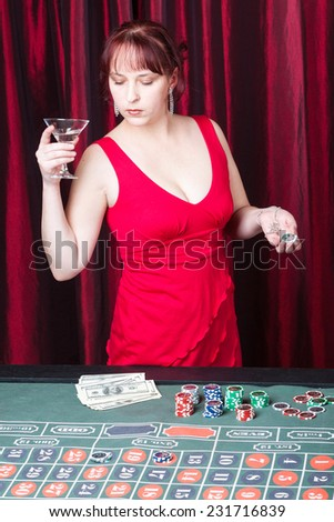 young woman with drinking playing in casino - stock photo