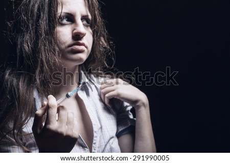 Young woman with drug addiction on dark backgroundÃ?? Focus on syringe - stock photo
