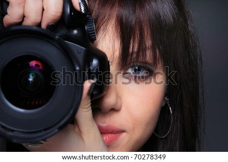 Young woman with DSLR over dark background