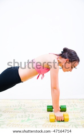 Young woman with dumbbells doing a push up fitness exercise. - stock photo