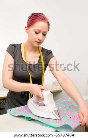 Young woman with electric iron - stock photo