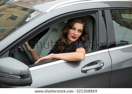 Young woman with elegant hairstyle and red lips sitting in car - stock photo