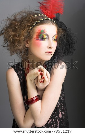 Young woman with  fashion creative visage and with feathers in her hair.