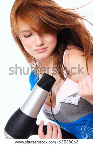 young woman with fashion hairstyle holding hairdryer and listen to music - stock photo