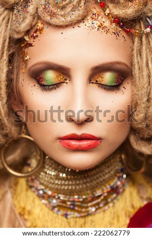 young woman with fashion makeup and closed eyes on brown background