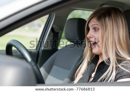 Young woman with fear in eyes driving car - hands down from steering wheel - stock photo