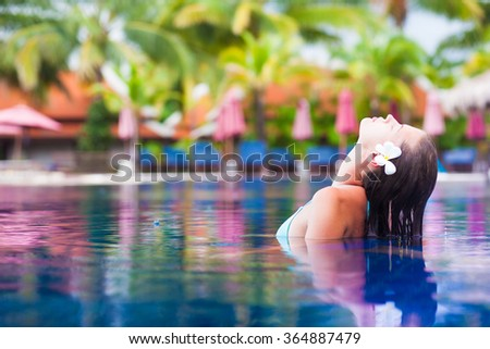 young woman with flower in hair taking spa in luxury pool - stock photo