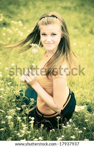 Young woman with flower on a summer field. Yellow and green tint. - stock photo
