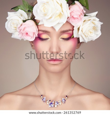 Young woman with flowers crown. Beauty model girl.Beautiful Girl with flowers on her head.Professional make-up - stock photo
