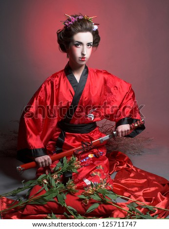 Young woman with flowers in her hair in red kimono and with sword